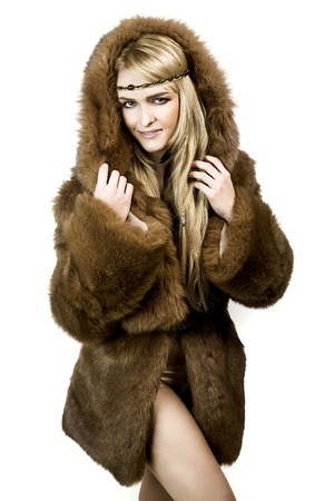 Attractive blonde girl with long hair dressed in a fur coat with  with hood with sexi expression
