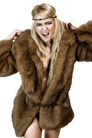 Blonde girl with long hair dressed in a fur coat with combative expression Standard-Bild