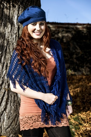 The beautiful girl with long red hair standing near a tree in autumn dressed in scarf