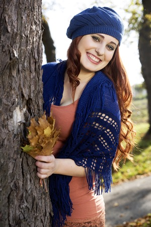 The beautiful girl with long red hair standing near a tree in autumn and holding leaves