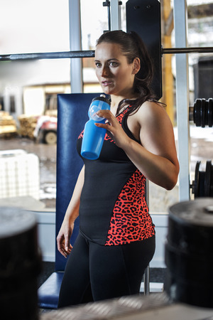 young woman after  exercise in the fitness gym with drink