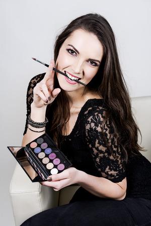 Das schöne Mädchen tragen schwarze T-Shirt mit Palette Augenschminke und Pinsel