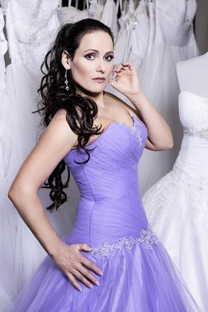 bridal salon: The beuatiful woman in bridal salon dressed in  a purple evening dress Stock Photo