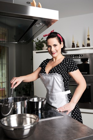pinafore: the housewife in pin up style cooking meal. She wearing dress with pinafore