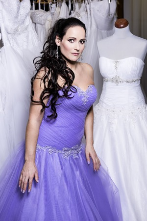 The beautiful woman in bridal salon dressed in  a purple evening dress