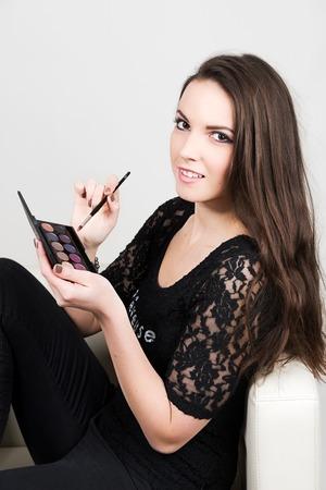Das schöne Mädchen tragen schwarze T-Shirt mit Palettenaugenschminke und Pinsel