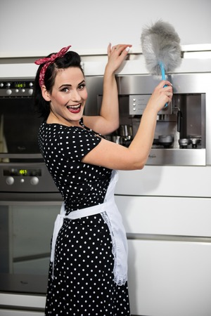 the housewife in  pin up style cleaning dust on the furniture