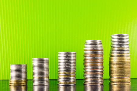 Pyramid gold and silver coins on a green background and dark desktop Stock Photo