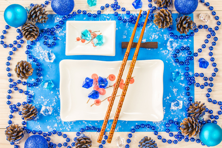Maki sushi on background Christmas plate of sushi on a blue background with beads and cones Stock Photo