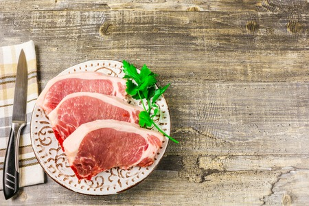 white backing: A white plate of raw sliced meat on wooden table, top view. Food, a knife, branches of greens