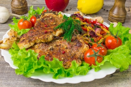 Pork steak with a fork lettuce tomatoes with dill, lemon and Apple in the background, close-up view. Grey food background on wooden table