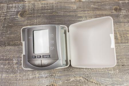 tonometer: Digital sphygmomanometer blood pressure monitor on the background of wooden table. Tonometer Stock Photo