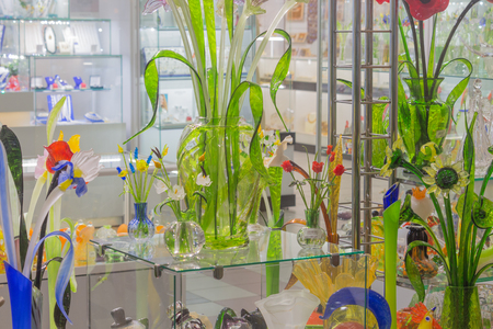 Flowers of glass and crystal. Souvenirs in St. Petersburg. Beautiful storefront colors of glass. Jugs and pots for flowers