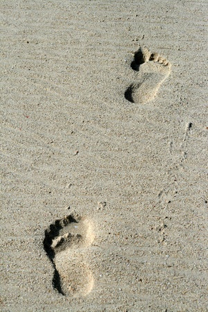 Two footprints on a sandy beach.