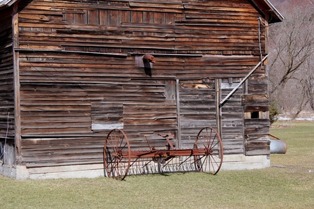 A vintage antique hay rake sits beside old, weathered farm building in a picturesque setting. photo