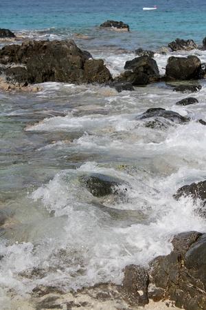 Gentle waves caress rocks along a Caribbean shore.