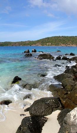 Waves gently caress the rocks along a Caribbean shore.
