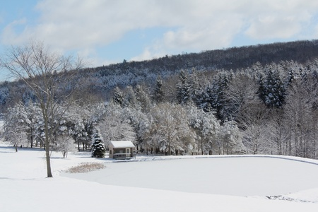 A snow-covered rural pond scene
