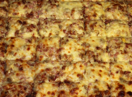 Slices of a sheet pizza are ready to be served.  Imagens