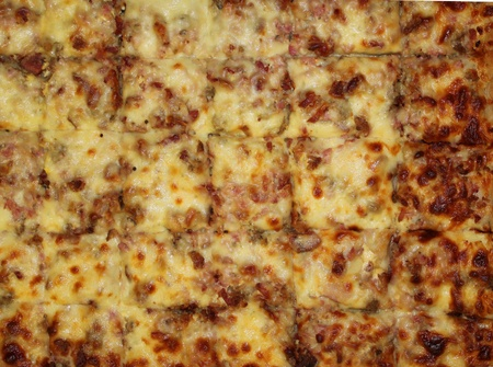 Slices of a sheet pizza are ready to be served.  Banco de Imagens