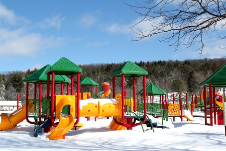 Snow-bound playground equipment at a rural park.