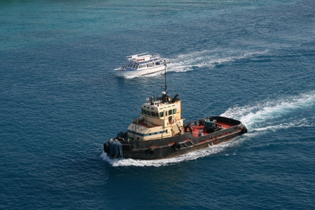 overtaken: A colorful harbor tug is overtaken along a waterway by a smaller pleasure boat. Stock Photo