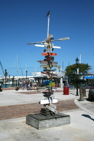 A colorful wooden sign at a Key West marina indicates directions and distances to dozens of exotic destinations worldwide.