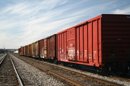 A freight train line of boxcars passing through a rail yard. Stock fotó