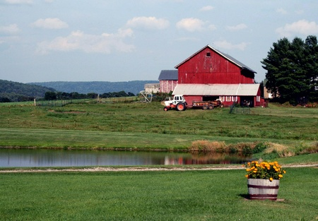 adds: A red barn adds a splash of color to a pastoral farm scene. Stock Photo