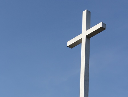 A white Christian cross stands out  against a deep blue blue sky.