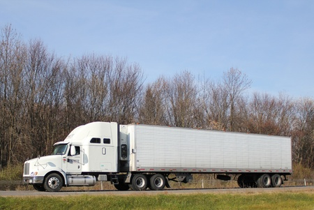 A tractor-trailer truck travels along an interstate highway.