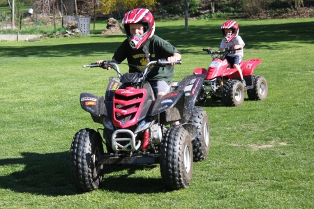 Two brothers enjoy a warm Spring day riding their ATV