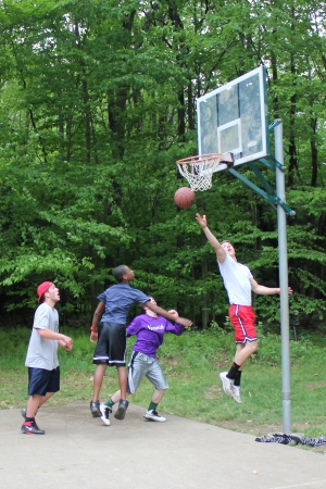 A player goes for a lay-up during a pick-up neighborhood basketball game as his opponents tries to block him  Redakční