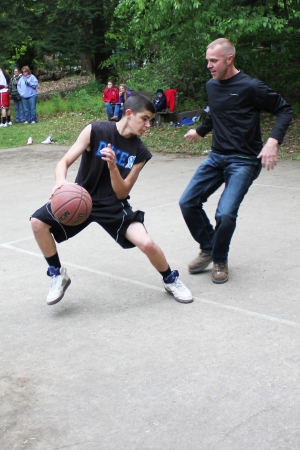 A player makes a move during a pick-up neighborhood basketball game as his opponent tries to block him