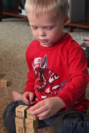 A little boy stacks wooden blocks atop one another as he plays by himself at home