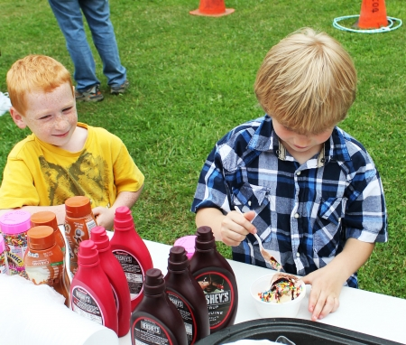 finishing touches: A young boy adds the finishing touches to an ice cream sundae at a summer outdoor event as another boy waits his turn
