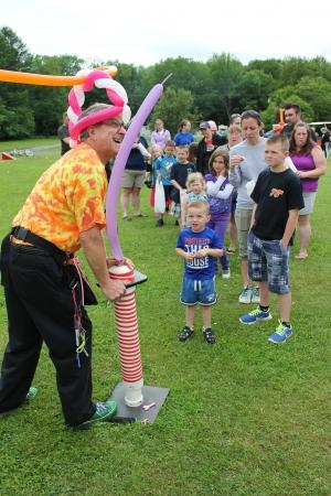 novelties: A man pumps air into a balloon as kids wait in line for a balloon at an outdoor children