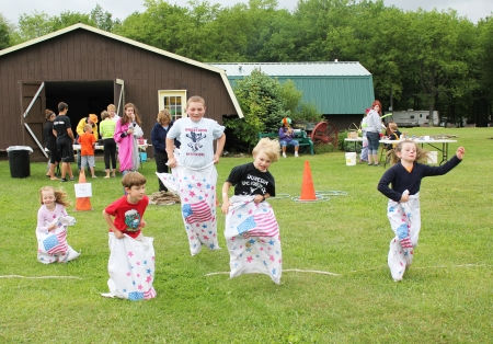 Kids hop up and down during a sack race at a children Editorial