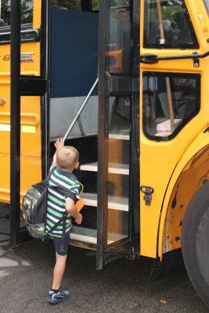 first day: A little boy boards a school bus on his way to his first day at school  Editorial