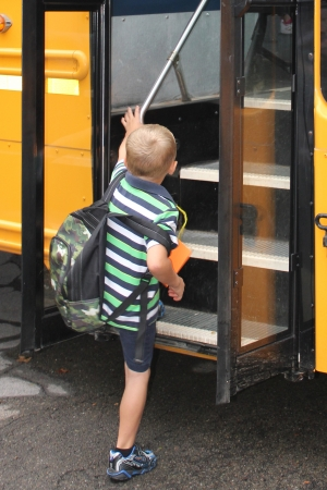 A little boy boards a school bus on his way to his first day at school  Publikacyjne