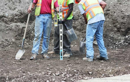 devise: Workmen on the site of a major new interstate highway interchange construction project using a devise to measure the depth of section of dirt   Editorial