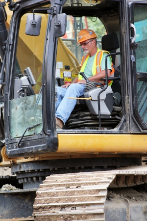 heavy equipment operator: A front end loader heavy equipment operator in the cab of his machine on a major interstate highway interchange project