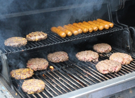 Hot dogs and hamburgers being placed on an outdoor backyard grill for a weekend cookout.
