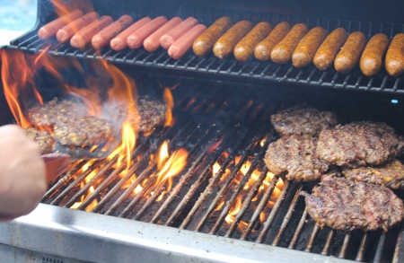 Flames flare up as hot dogs and hamburgers being tended by the chef on an outdoor backyard grill during a weekend cookout.