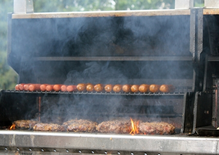 sizzle: Hot dogs and hamburgers generate smoke as they sizzle on an outdoor backyard grill during a weekend cookout.  Stock Photo
