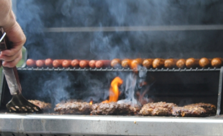 Hot dogs and hamburgers being tended by the chef on an outdoor backyard grill during a weekend cookout.