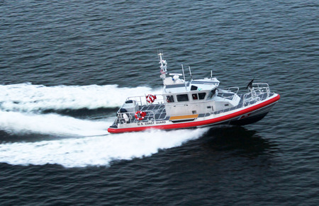 homeland: An armed U.S. Coast Guard patrol boat shadowing a cruise ship sailing along   the Chesapeake Bay off the coast of the State of Delaware, USA.  The armament is mounted on the bow of the boat. Editorial