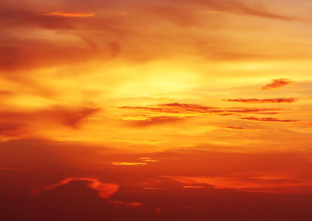 The sun setting n the horizon creates the appearance of burning clouds