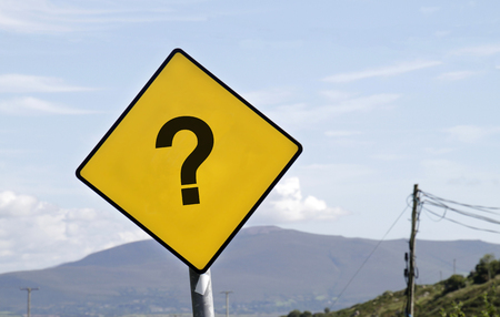 Yellow road warning sign with question mark in front of curve
