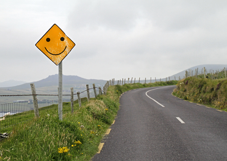 Yellow road warning sign with smiley ahead of curve Фото со стока